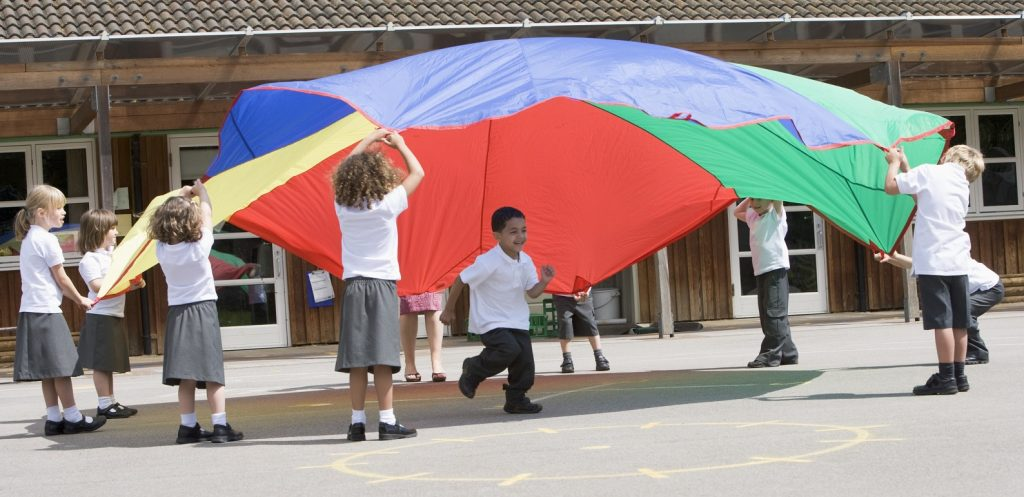 Young children playing with a parachute in the playground